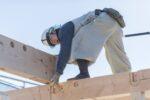手作業で家を組み立てる大工